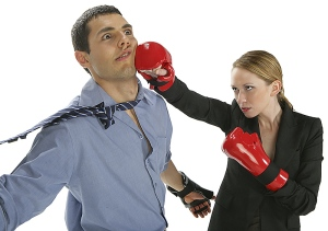 Corporate woman with boxing gloves striking a man in a tie