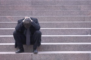 Upset man on stairs with his head in his hands