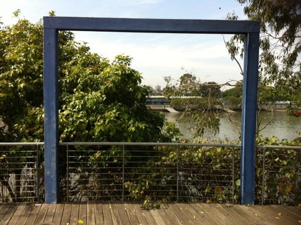 A wooden frame by the river, view obscured by trees.