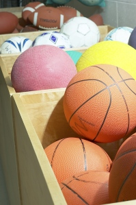 Boxes of different balls, basketballs, volleyballs, footballs