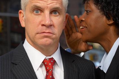 Woman whispering in a man's ear.